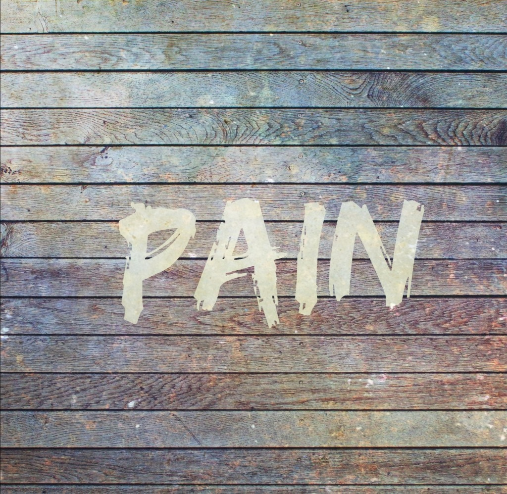 "Board wall, distressed. ""PAIN"" painted on top in white."