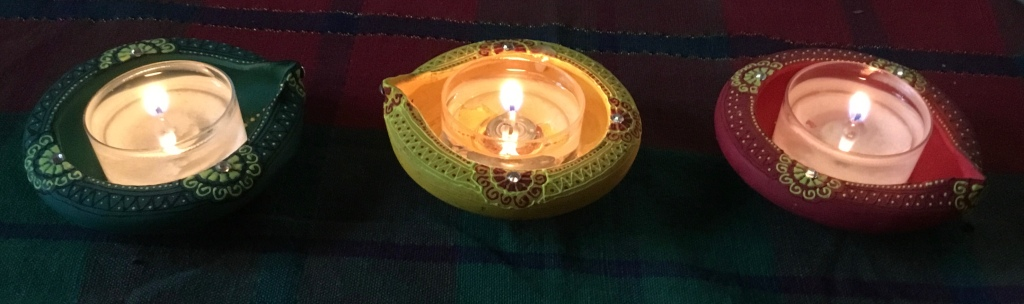 Three small circular incense holder, circular, bright red, green, and yellow, with lit tea candles inside.