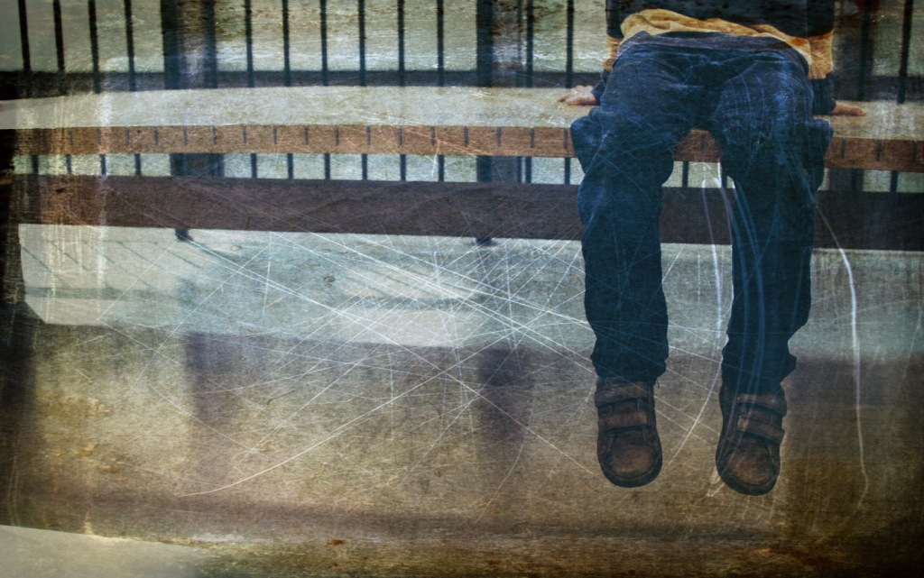 Young child sitting on high bench, with a railed banister behind. Only dangling legs, shoes, and a strip of bunched top are showing. The top appears to be striped yellow and brown, with long sleeves. The child wears jeans and brown leather shoes with Velcro straps. The original photograph is not distressed but I distressed it.