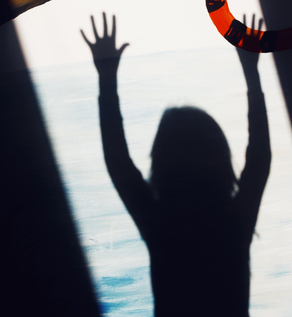 A backlit girl in silhouette has her hands raised in a door-like opening. Beyond the opening there is a large body of water, out of focus. The larger context, which I have cropped out, suggests that the girl is about to jump into water, or use a zipline. The cropped image gives a sense of isolation, surrender, and a jump into the unknown.